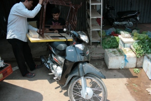 How things get done in Asia: strapping a sewing machine's base to a bike... eep.